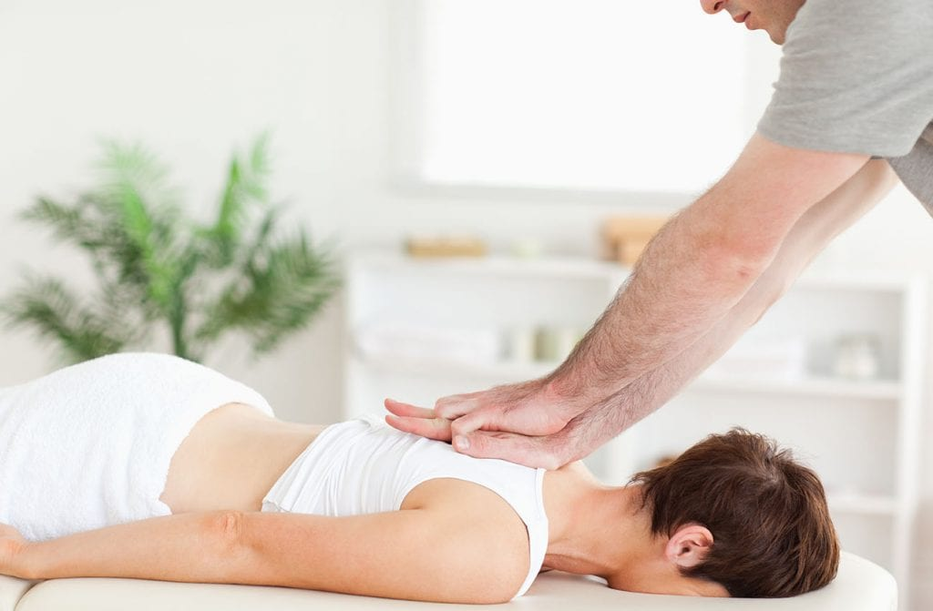 chiropractor adjusting upper back pain