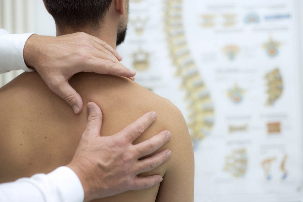 Chiropractor working on mans back for whiplash